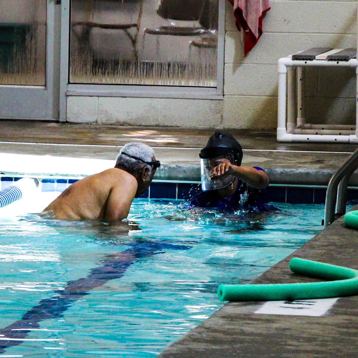 Instructor demonstrating a swimming stroke to student