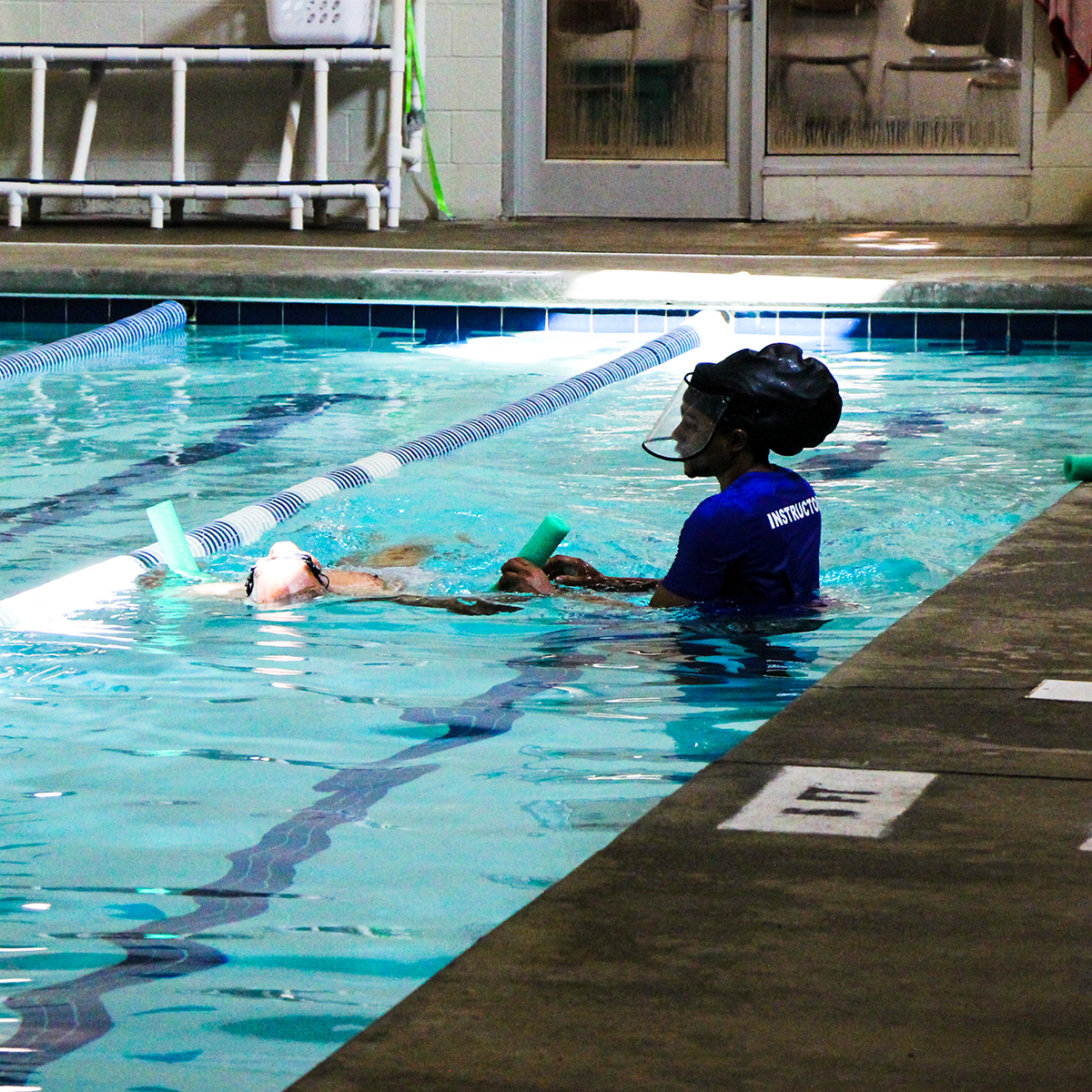 Student practicing back floating with instructor